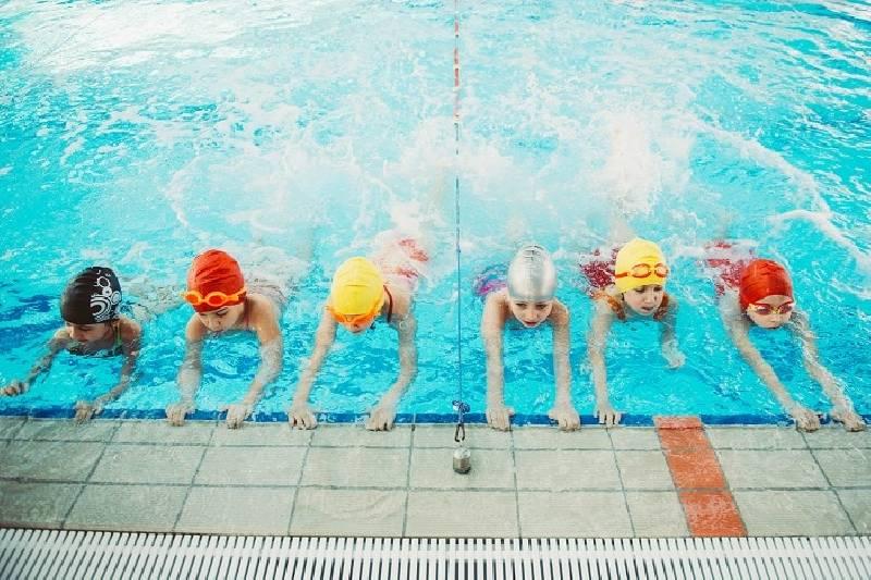 Les enfants heureux se regroupent en classe de piscine pour apprendre à nager.